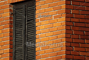 House Wall Made Of Bricks With Window Closed Wooden Shades Stock Photo