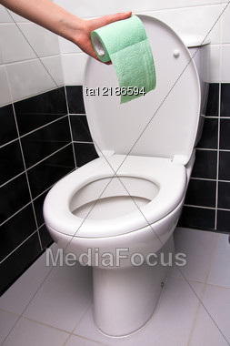 Human Hand Holding Green Toilet Paper On The Background Of Toilet Bowl Stock Photo