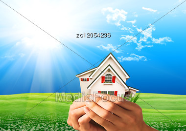 Human Hands Holding Model Of A House Against Nature Background Stock Photo