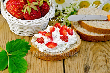 Hunk Of Bread With Cottage Cheese Cream, Strawberries, A Basket With Berries, Leaf, Flower Daisies On A Background Of Wooden Boards Stock Photo