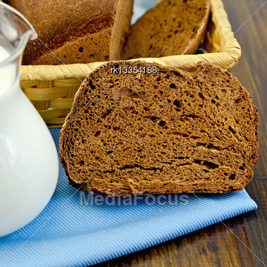 Hunk Of Homemade Rye Bread, Wicker Basket With Bread On A Blue Napkin On A Wooden Boards Background Stock Photo