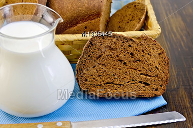 Hunk Of Homemade Rye Bread, Wicker Basket With Bread, Knife On Blue Napkin Against A Wooden Board Stock Photo