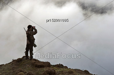 Hunter Looking For Game Animals Such As Chamois, Deer Or Tahr, In South Westland's Southern Alps, New Zealand Stock Photo