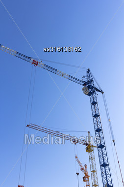 Industrial Landscape, Building Crane Against The Blue Sky Stock Photo