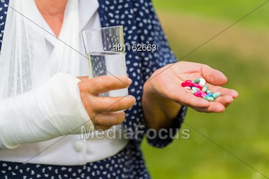 Injured Elderly Woman Hand Selecting Among Pharmaceutical Pills And Homeopathic Medicine Outdoors Stock Photo