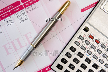 Ink Pen,calculator And Payroll Summary Details Stock Photo