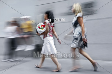 Intentional Blur Of A Woman Walking On The Street With Bouquet Of Flowers,second Woman Walking By Stock Photo