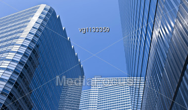 Intentional Distortion Abstract Low Angle View At Modern Corporate Buildings In Perspective With Blue Sky Reflection Stock Photo