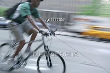 Intentional Motion Blur Abstract Of A Bike Rider Moving Along With Traffic, Alternative Urban Transportation Concept Stock Photo