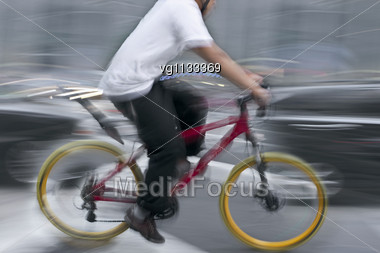 Intentional Motion Blur Abstract Of A Male Bike Rider Moving Along With Traffic, Alternative Urban Transportation Concept Stock Photo