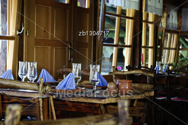 Interion Of Traditional Country Restaurant Room In Serbia With Chairs And Tables Made Of Raw Wood. Stock Photo
