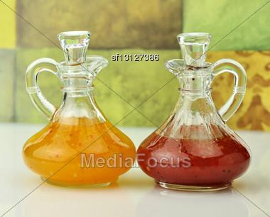 Italian And Raspberry Vinaigrette Salad Dressings In Glass Bottles Stock Photo