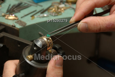 Jeweller Positions A Natural Emerald In A Gold Ring Stock Photo