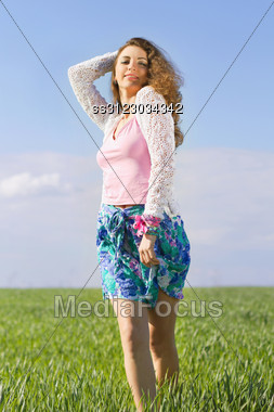 Joyful Pretty Young Woman In A Green Field Stock Photo