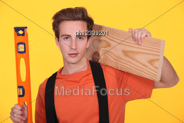 Junior Carpenter Posing With Ruler And Lumber Over Shoulder Stock Photo