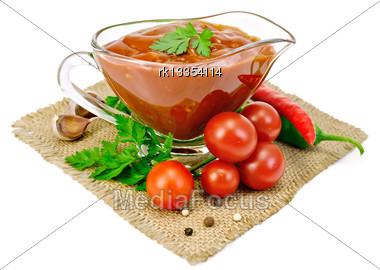 Ketchup In A Glass Sauceboat With Tomatoes And Parsley, Hot Pepper, Garlic On A Sacking Isolated On A White Background Stock Photo