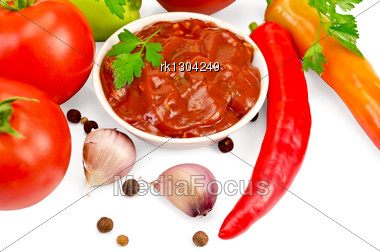 Ketchup In A White Cup, Tomatoes, Two Red Fresh Hot Pepper, Garlic, Peppercorns, Mustard, Parsley Stock Photo