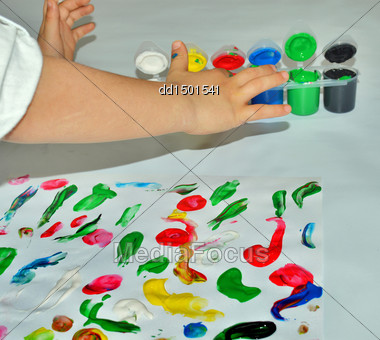 Kid Paints With Her Fingers With Different Color Paint Stock Photo