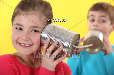 Kids Using Tin Cans To Communicate Stock Photo
