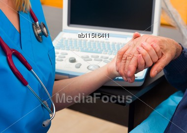 Kind Doctor Giving Supporting Hand For Elderly Man With Serious Disease Stock Photo