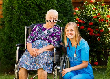 Kind Doctor Taking Care Of Elderly Woman At The Nursing Home Stock Photo
