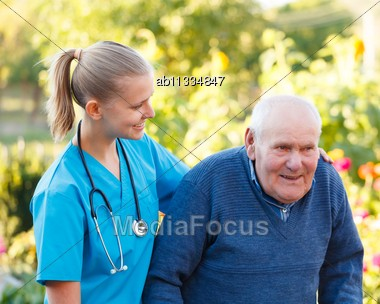 Kind Helpful Doctor Giving Support To Her Elderly Patient Stock Photo