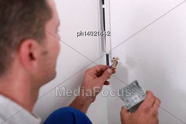 Laborer Repairing Electrical Installation Stock Photo