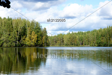 Lake And Trees On A Background Of The Blue Sky Stock Photo