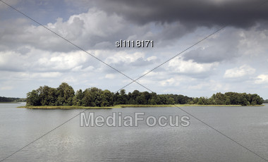 Lake Under Dark Clouds. Forest On A Islands Stock Photo
