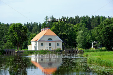 Landscape With Houses And A Forest On Coast Of A Pond Stock Photo