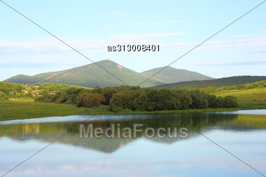 Landscape Mountain Lake Against The Sky In Clouds Stock Photo