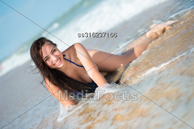 Laughing Young Brunette Lying On The Beach Stock Photo