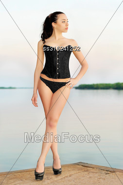Leggy Brunette Wearing Black Panties And Corset Posing On The Pier Stock Photo