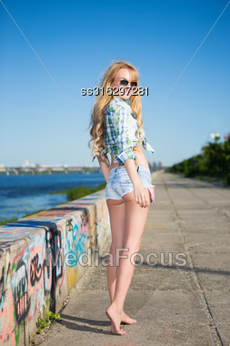 Leggy Young Blond Woman In Jeans Shorts Posing Outdoors Stock Photo