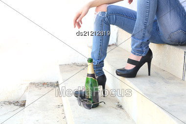 Legs And High Heels Of The Female Sitting On The Stairs Stock Photo