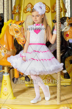 Little Beautiful Girl In Pink And White Dress Standing On The Carousel Stock Photo