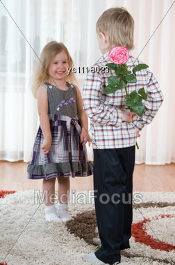 Little Boy Gives To The Girl A Flowers Stock Photo