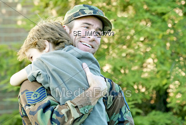 Little Boy Hugging Military Dad Stock Photo