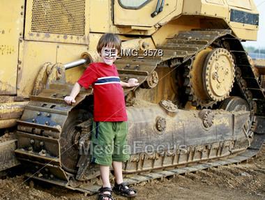 Little Boy Leaning on Bulldozer Stock Photo