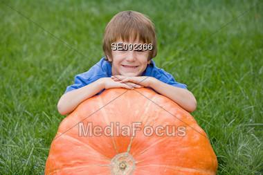 Little Boy Leaning on a Huge Pumpkin Stock Photo