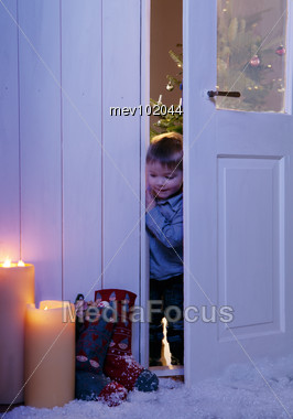 Little Boy Looking At Christmas Stockings Stock Photo