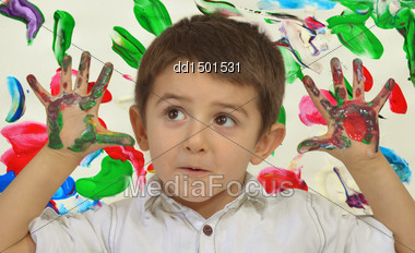 Little Boy Painting With Hands With Different Color Paint On His Palms Stock Photo