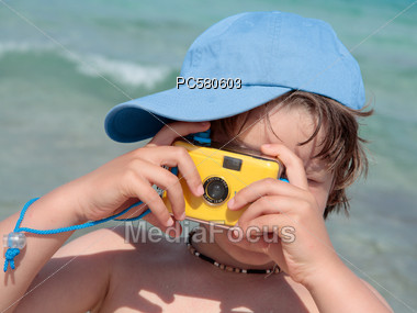 Little boy with a Simple Camera on the Beach Stock Photo
