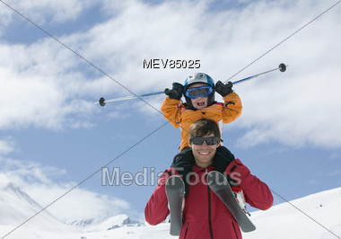 Little Boy Sits On Father's Shoulder, Skiing Stock Photo