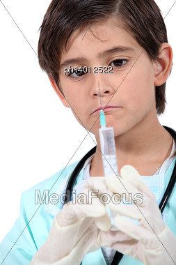Little Boy With Syringe Dressed As Doctor Stock Photo