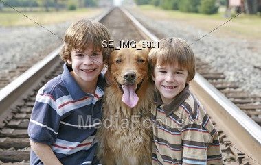 Little Boys on the Railroad Tracks with Dog Stock Photo