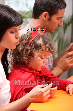 Little Child Dressed Up In Little Devil And His Parents, His Mother Is Varnishing His Child's Snails Stock Photo