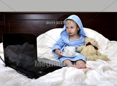 Little Girl In A Bathrobe Relaxing On The Bed After A Shower With Cup Of Tea And Laptop Stock Photo