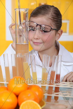 Little Girl Conducting Experiment On Oranges Stock Photo