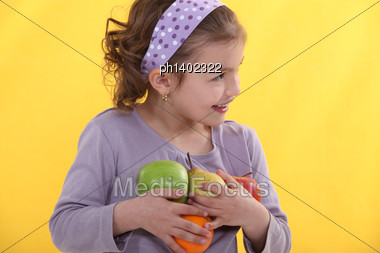 Little Girl With Her Arms Full Of Fruits Stock Photo